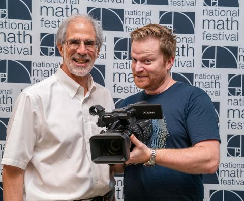 Numberphile's Brady Haran with camera and MSRI's David Eisenbud at National Math Festival 2019