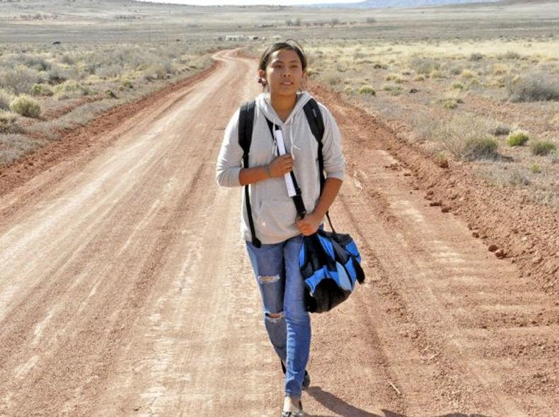 Young woman walking with a shoulder bag on a dirt road in the desert