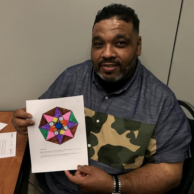 Man holding mathematical coloring page - National Math Festival 2019