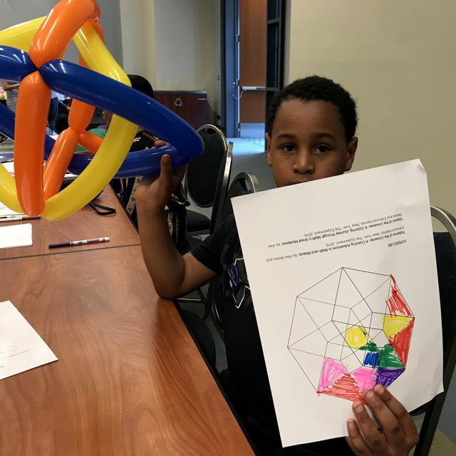 Boy holding mathematical coloring page and balloon Sculpture - National Math Festival 2019