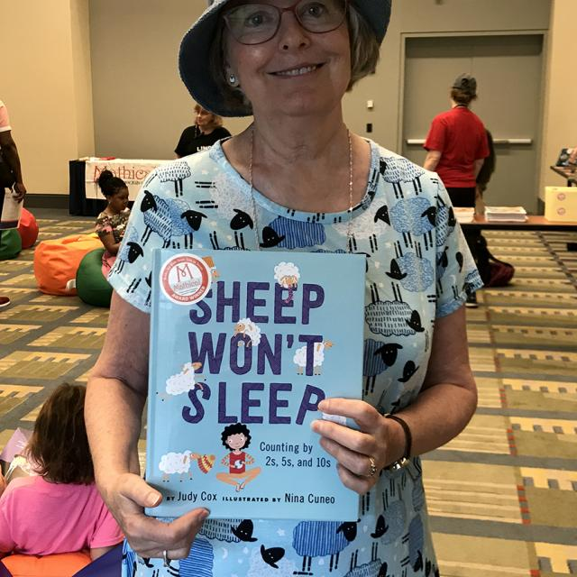 Mathical Author Judy Cox holding book - Sheep Won't Sleep - National Math Festival 2019