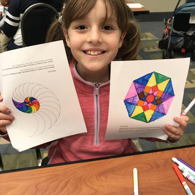 Girl holding mathematical coloring page - National Math Festival 2019