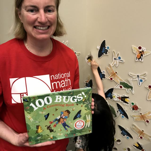 Mathical Author Kate Narita holding 100 Bugs: A Counting Book - National Math Festival 2019