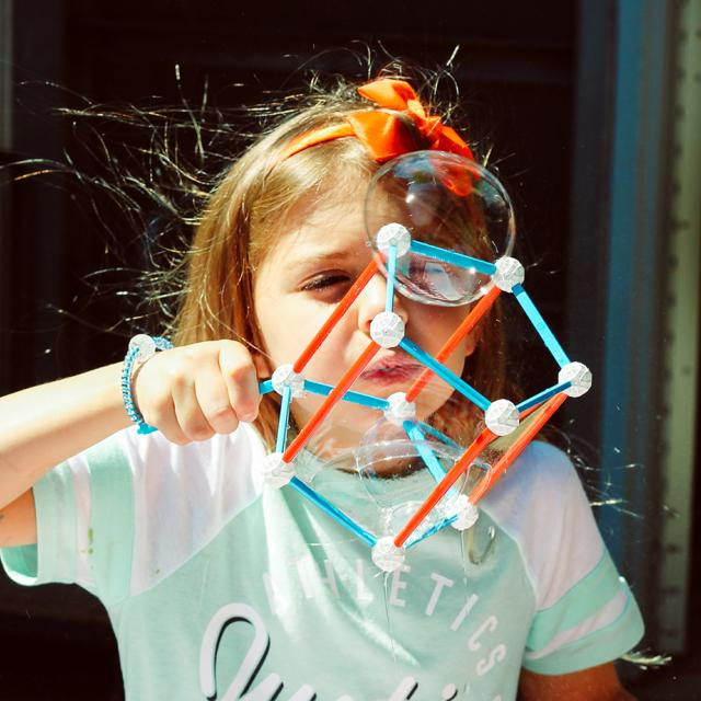 girl playing with bubble shapes